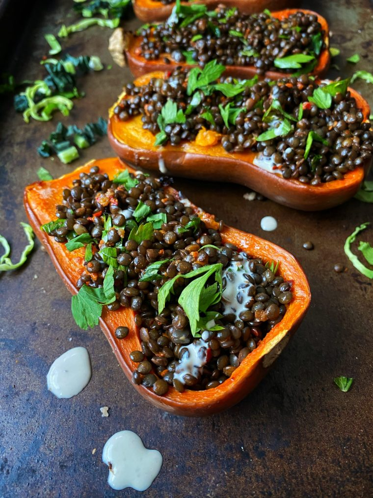 Always on the hunt for delicious, vegetarian Thanksgiving main dishes? Look no further than these delicious butternut (or honey nut) squashes glazed with coconut oil, roasted and stuffed with warm and spicy harissa lentils salad. Topped with a lemony tahini sauce, it makes for a delicious main perfect for any time of year! #thecuttingveg #eatrealfood #vegetarian #thanksgiving