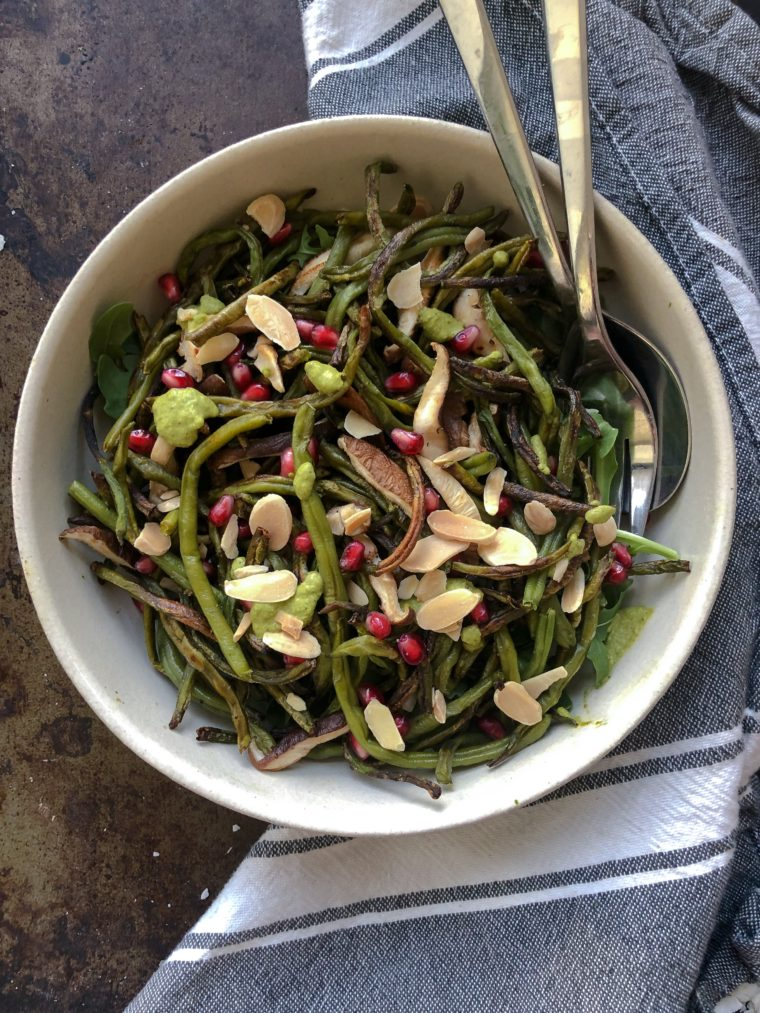 Za'atar Roasted Green Beans topped with a green harissa, almonds, and pomegranate seeds. The perfect addition to any holiday table. #thecuttingveg #eatrealfood #thanksgivingside