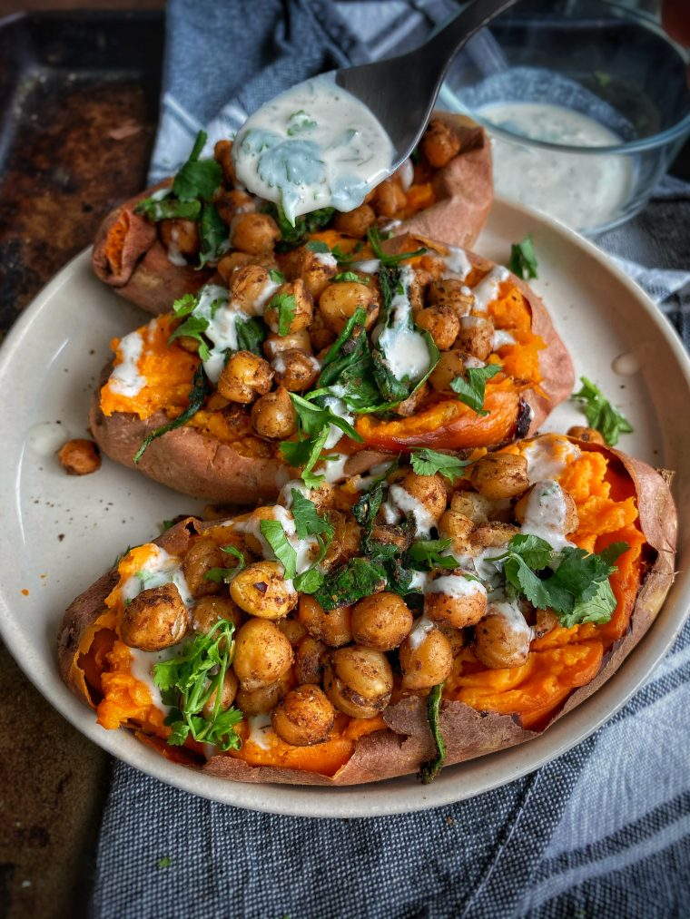 These Roasted Sweet Potatoes with Shawarma Chickpeas are the coziest little meal for those chilly nights. Crispy chickpeas tossed in warming spices are stuffed inside roasted sweet potatoes and drizzled with a lemon tahini sauce. #thecuttingveg #sweetpotatoes #roastedchickpeas #vegandinner