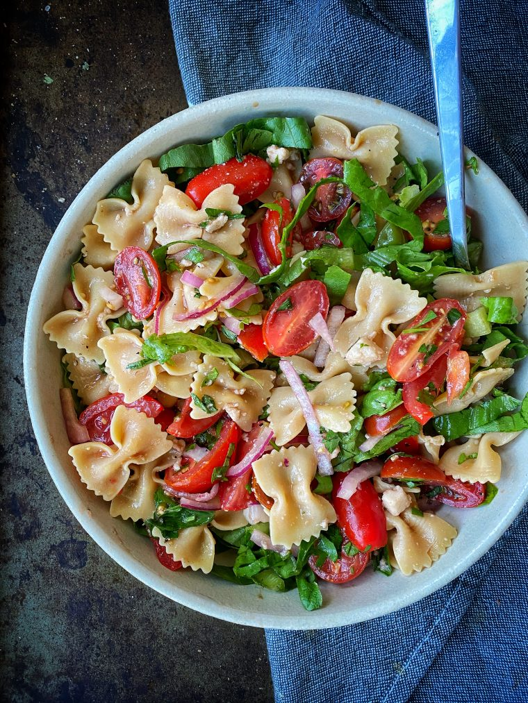 A dairy free take on your favorite summer salad, this Vegan Caprese Pasta Salad is the perfect minimal cook meal for these hot summer nights! Fresh tomatoes, basil, and vegan mozzarella tossed with balsamic vinegar and olive oil, it is the flipping best combo have for a main meal or on the side of your BBQ. #thecuttingveg #eatrealfood #caprese #pastasalad